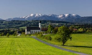 church with the german alps mountain range in the background