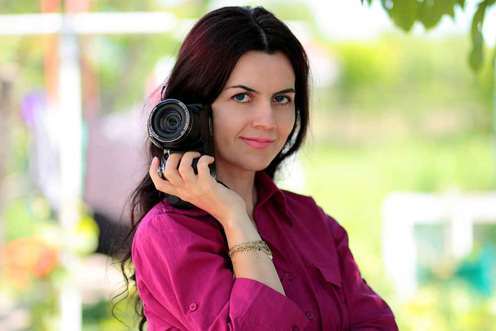 portrait of a woman holding an a6000 camera