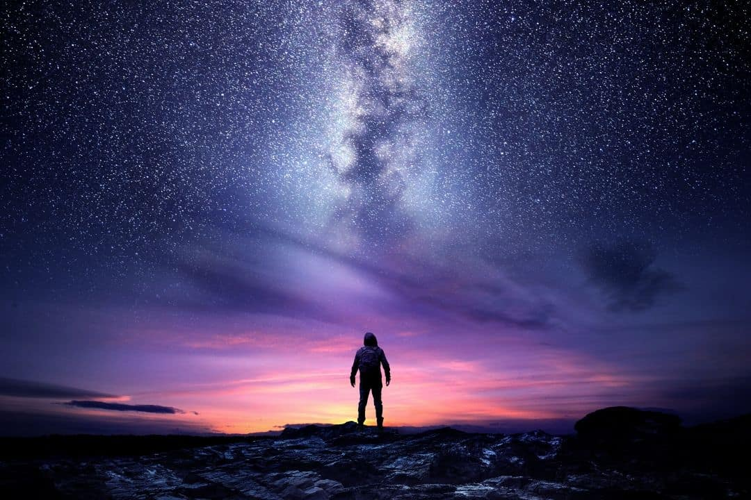 astrophotographer with the milky way in the background