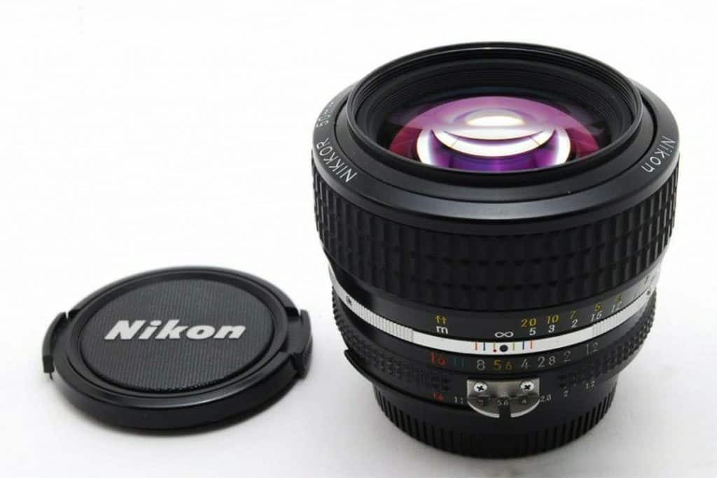 Nikon AI-S FX NIKKOR 50mm f/1.2 Fixed Zoom Manual Focus Lens with its cap next to it