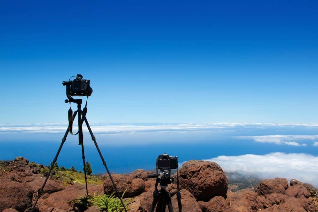 two nikon cameras on tripods at the edge of a cliff taking picture of the horizon