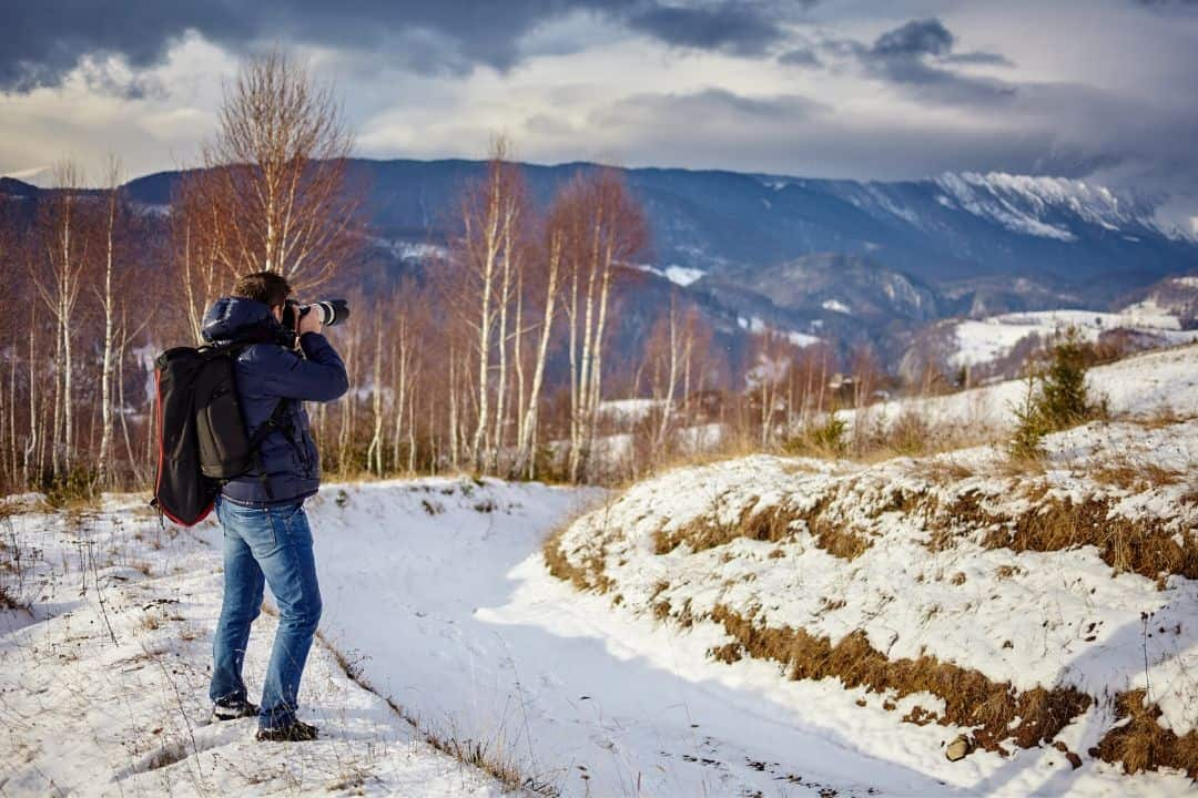 photographer taking a picture of a snowy mountain ridge