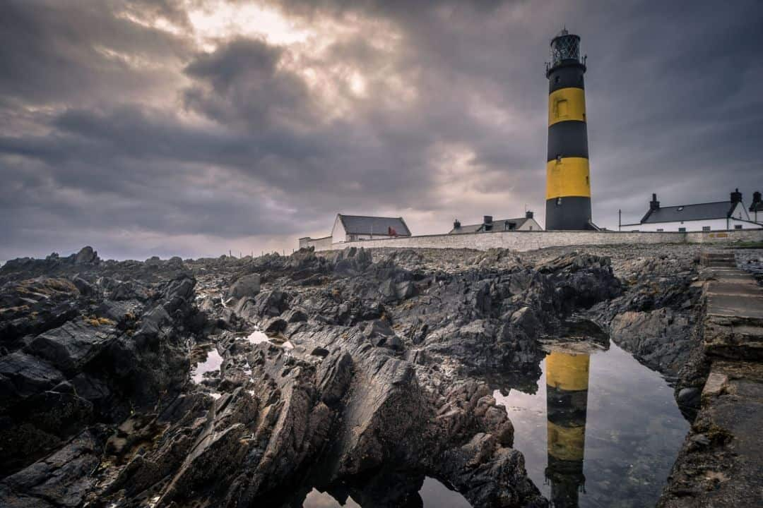 rocks and a lighthouse at a beach during low tide