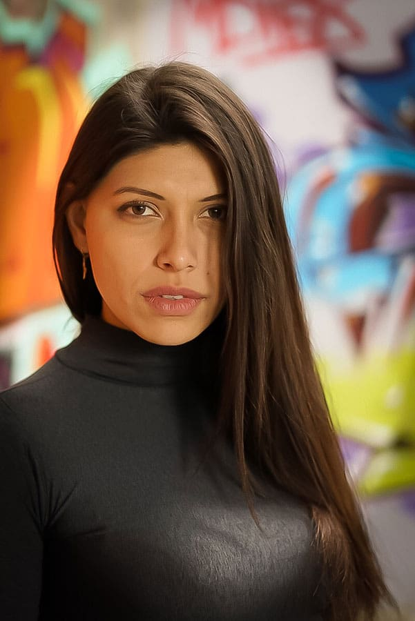 portait of a latina woman with grafiti in the background showing bokeh blur
