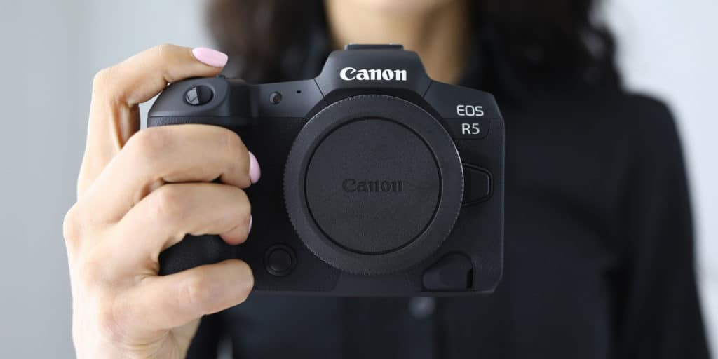 Woman holding a canon eos r5 without a lens