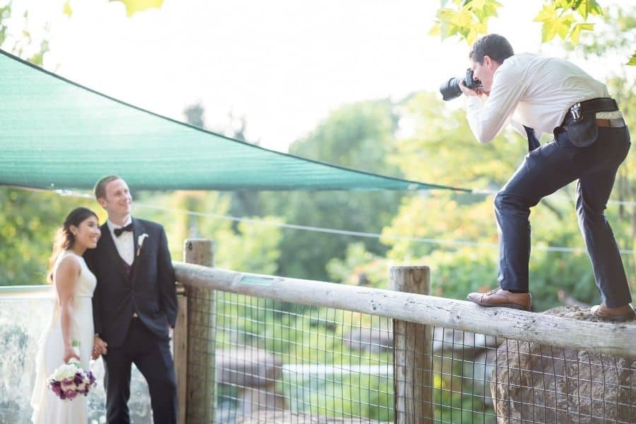 photographer taking a picture of the husband and wife during a wedding