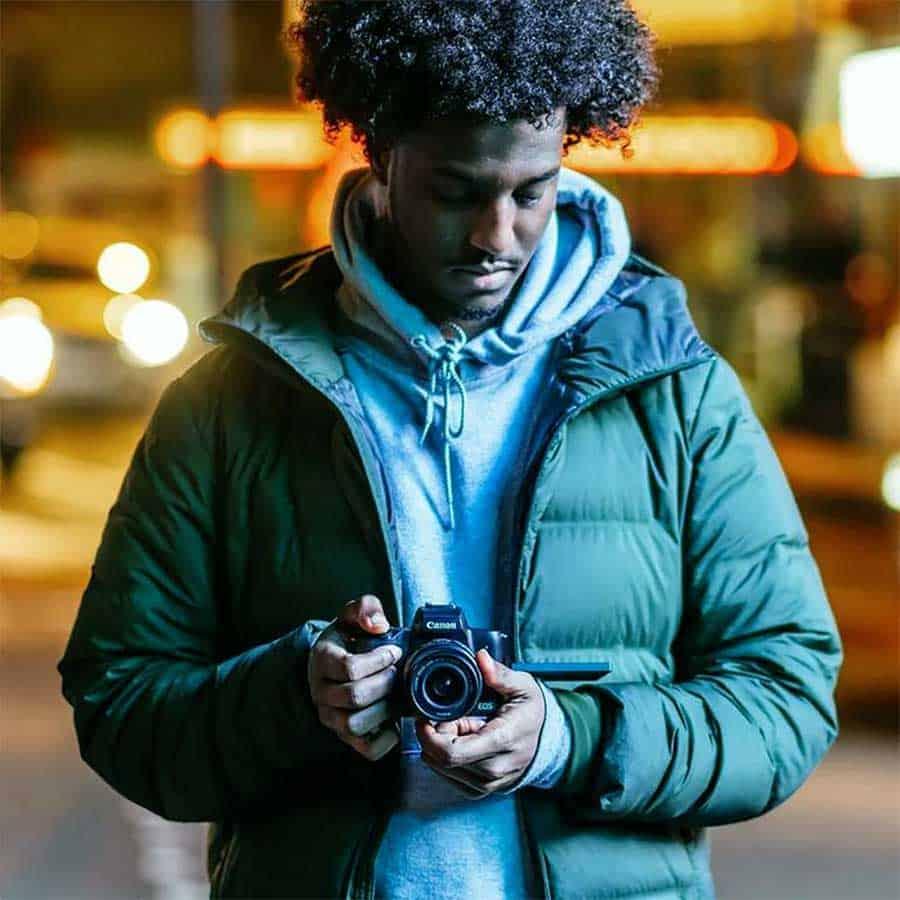 vlogger holding a m50 eos camera